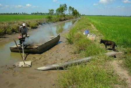 Máy bơm nhả khói nghi ngút nhưng không lên được giọt nước nào vì kênh trơ đáy - Ảnh: DUY KHANG